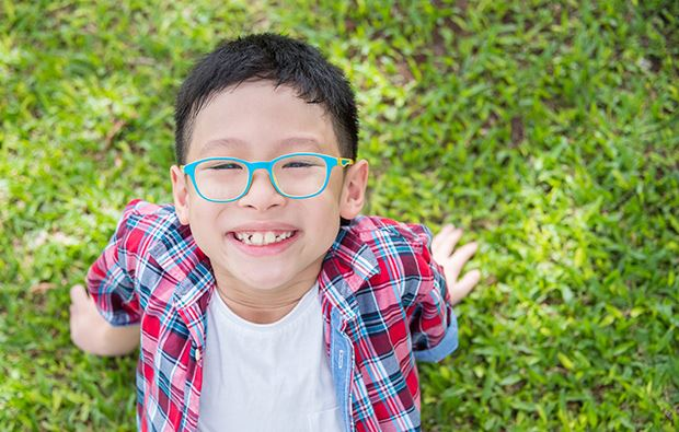 child in glasses outside in the sun